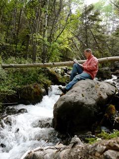 Joe McGarry sitting on rock next to Colorado stream reading